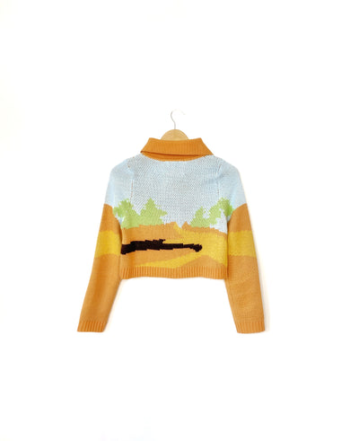 House of Sunny Daybreak Cardigan in Orange and Pastel. Daybreak Cardigan is inspired by sunsets and sunrise, designed by a U.K.-based independent design label, House of Sunny. Daybreak is a jacquard cardi with a large retro collar. Wear as a top or as a cardigan.