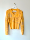 House of Sunny's hockney knit in amber color. This sweater has a removable sleeves so you can wear it as a long sleeve, or as a sweater vest. This is made in viscose and nylon blend in burnt, faded orange color.
