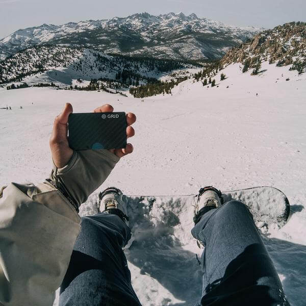 Male holding Carbon fiber wallet snowboarding in California