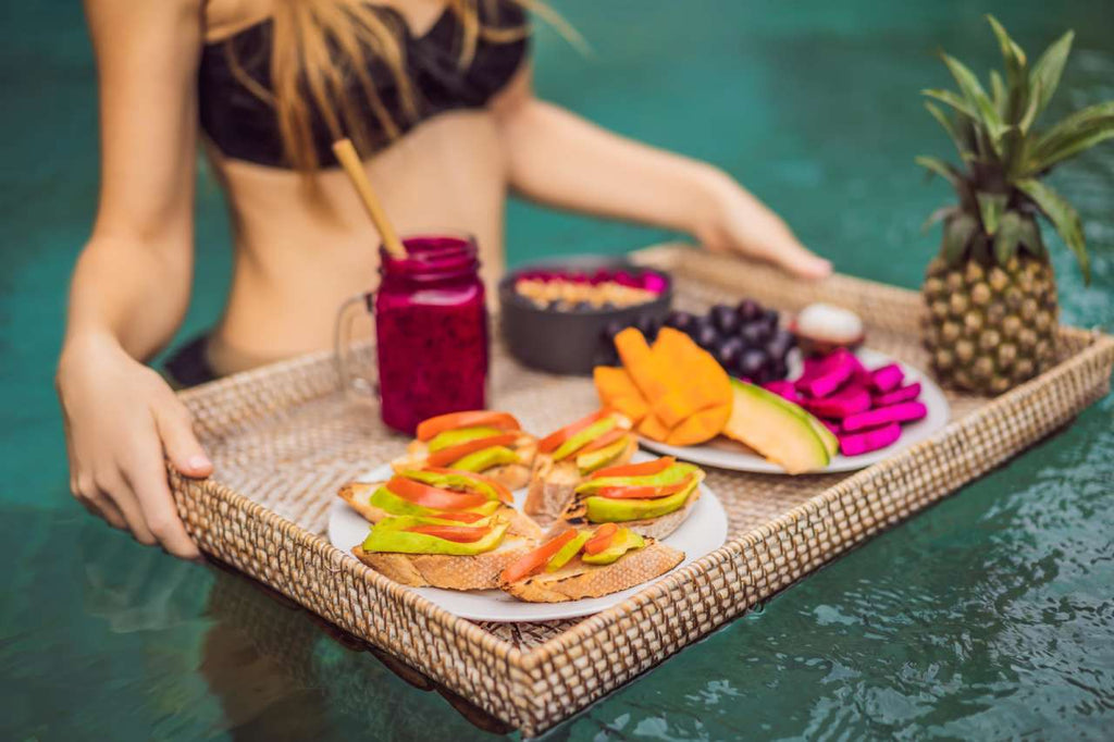 girl in a bikini taking her tropical lunch on a pool colorful drink and fruits