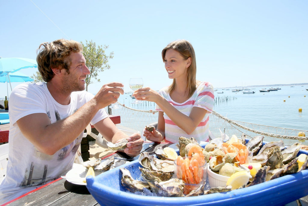 romantic couple eating by the beach seafood and drinks