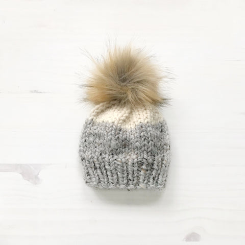 knitted hat, bottom half speckled gray, top half cream, with brown fur pom pom on the top