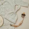 newborn gray beanie laying on top of gray onesie with wood bead pacifier clip attached to brown pacifier