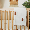 white blanket with rust colored half circles draped over the edge of a light wood crib