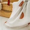white blanket with rust colored half circles draped over the edge of a basket