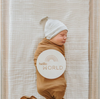 baby on white blanket, wrapped in rust blanket, with gray beanie on head