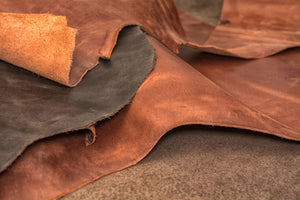 A few different pieces and types of leather all laying on top of each other.