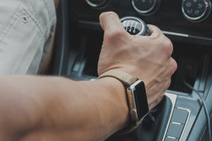 Male clenching gearshift sporting a leather premium Apple watch band, attached to Silver Apple watch