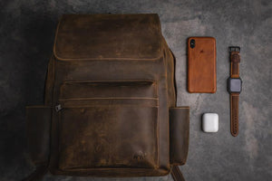 A flatlay of a leather backpack, a leather iPhone case, a leather Apple Watch band, and Airpods