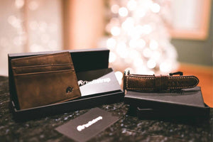 A Bullstrap leather Apple Watch band, leather wallet, and gift cards in focus with a lit Christmas tree in the background.