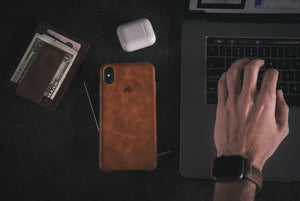 premium iphone case on table next to computer, wallet, and Apple Air Pods