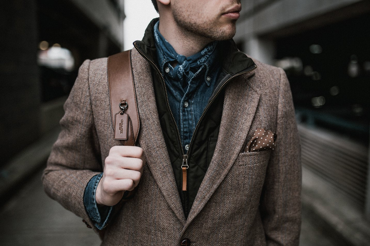 stylish man in a  business casual outfit  accessorizing with a modern pocket square, bandana, and leather backpack