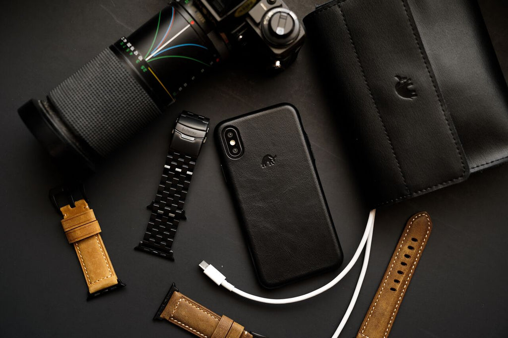 Flatlay of Bullstrap products: phone case, leather and metal mens watch straps, wallet, and camera