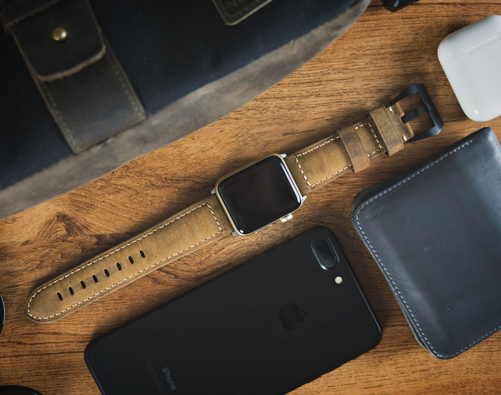 Flat lay on wood background of leather products: classic finish Apple Watch strap, black iPhone case, black wallet