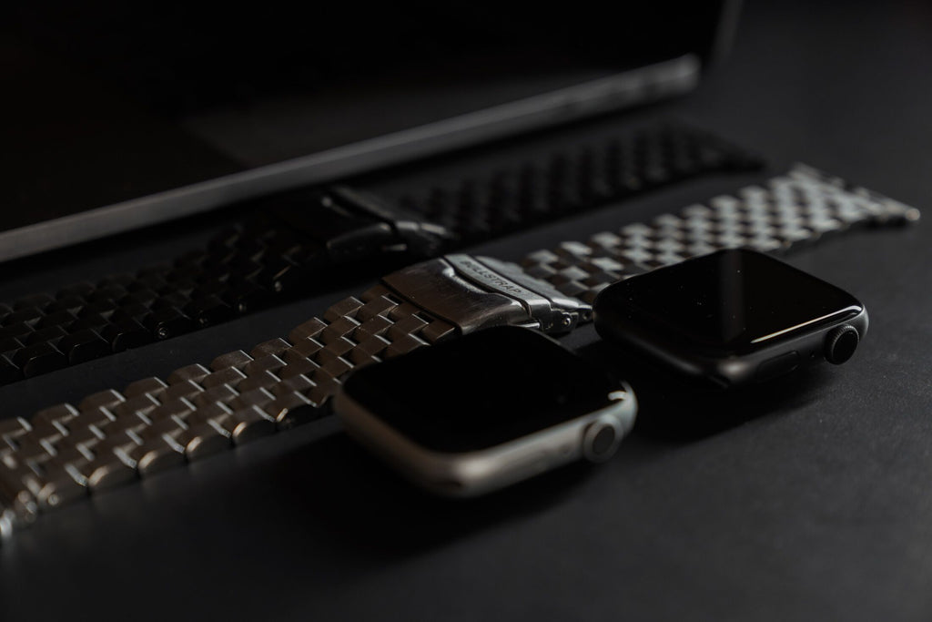 Black edition and silver metal Apple Watch straps next to Space Gray Aluminum Case and Silver Aluminum Case