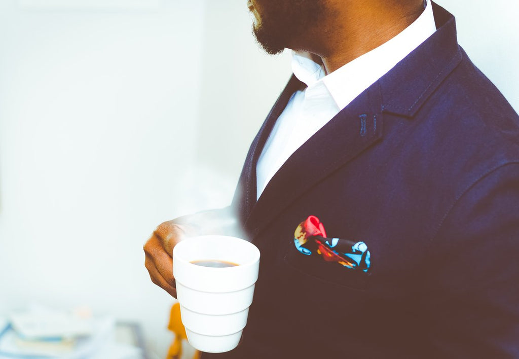 Man wearing blue suit jacket with colorful pocket square, holding a cup of coffee