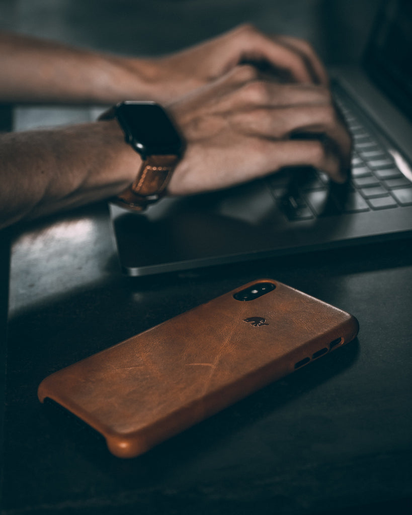 Brown Leather iPhone case next to man typing on computer