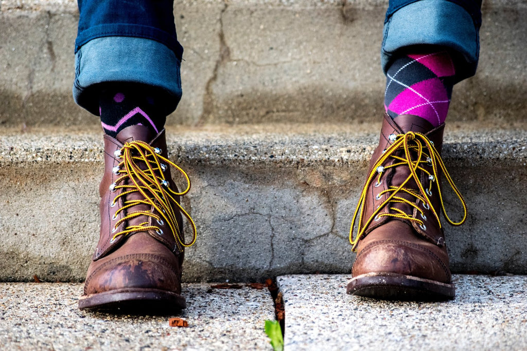 Man wearing brown leather lace up boots and mismatched fun patterned socks