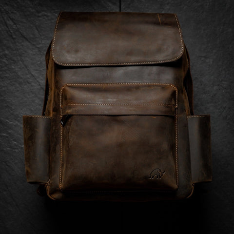 A durable leather backpack from Bullstrap placed on a plain, dark background