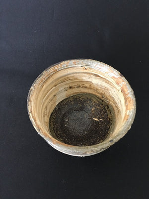 handmade Japanese ceramic cup in texture of shredded wheat and tones of coffee and cream