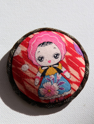 Kawaii dolly-san sits on red and white Japanese arrow print fabric brooch