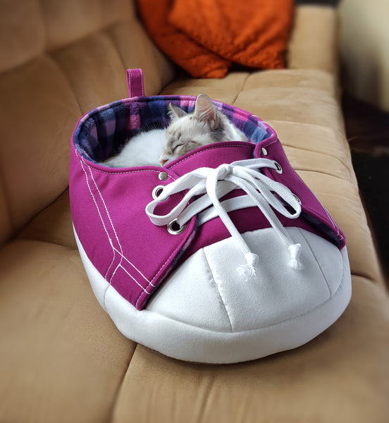 A cat sleeping inside of Purple Sneaker Pet Bed