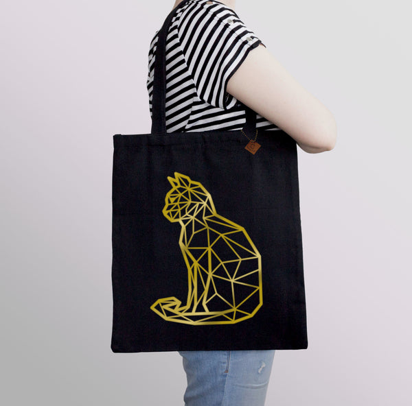 carrying a black tote bag with gold cat print
