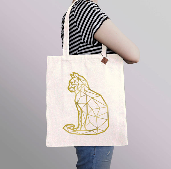 carrying a beige tote bag with gold cat print