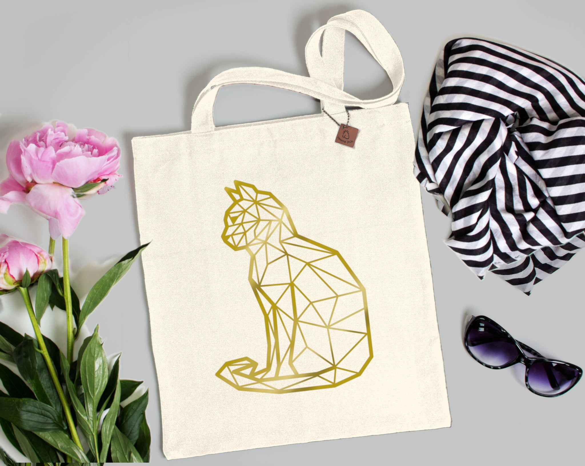 gold cat print on a beige tote bag
