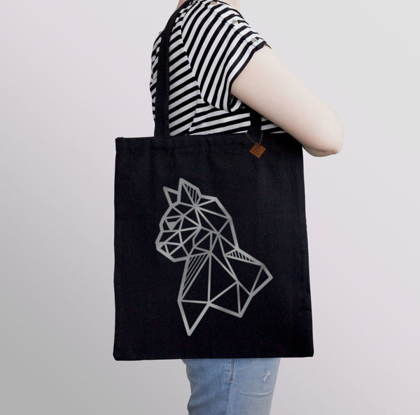 carrying a black tote bag with silver cat print