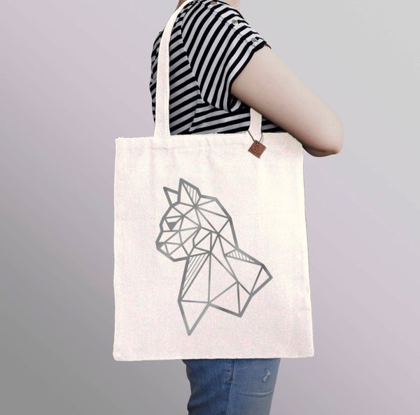 carrying a beige tote bag with silver cat print