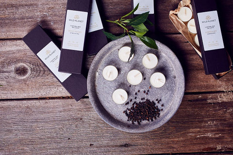Boxes of Scented Tea Lights on wooden table with six tea lights on grey metal tray with black peppercorns