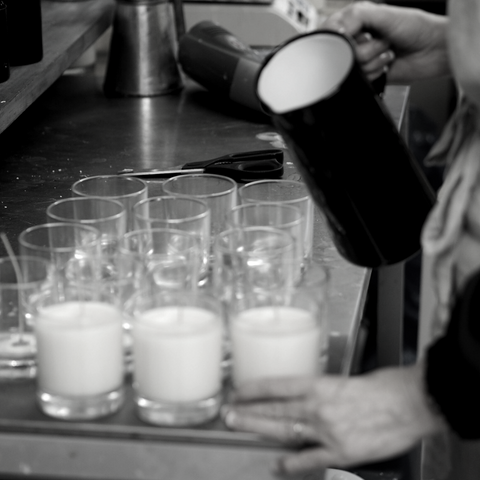 Black and white image of Luxury Scented candles and person hand pouring from black enamel just into empty glass candle containers on metal bency