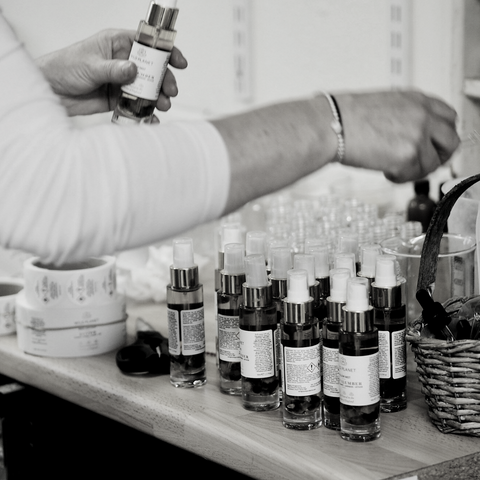 Black and white image of person sticking labels of Aura Spray Rejuvenate glass bottles with Carnelian crystals