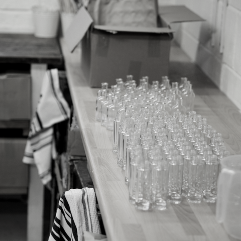 Aura Spray glass bottles on work bench ready to be filled in black and white