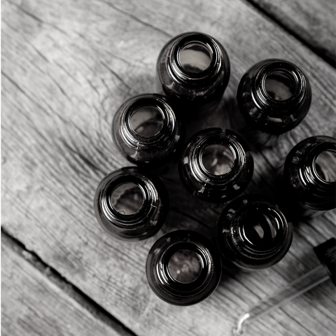 Black and white image of glass essential oil bottles and dropper