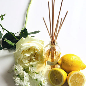 natural reed diffuser glass bottle with reed sticks next to fresh white flowers and lemons