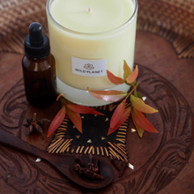 Soft Embers Orange and Clove Scented Candle on wooden dish, next to leaves and essential oil bottle