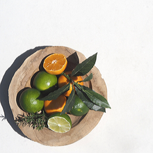 Wooden bowl of fresh fruit including cut limes and mandarins with fresh sprigs of rosemary