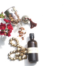 Amber glass bottle of patchouli essential oil next to glass bottle of dried rose petals, gold beads