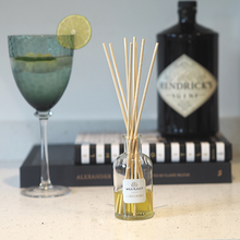 Limelight Natural Reed Diffuser glass bottle next to glass of gin and bottle of gin on two books