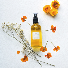 Orange Blossom Room Spray Glass atomiser bottle next to orange flowers by Wild Planet UK