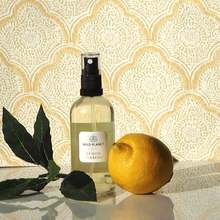 Essential Oil Room Spray glass bottle with in lemon verbena fragrance next to fresh lemon and leaves