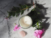 Top of Restore Candle jar next to pink flowers, green foliage and rose quartz on marble table