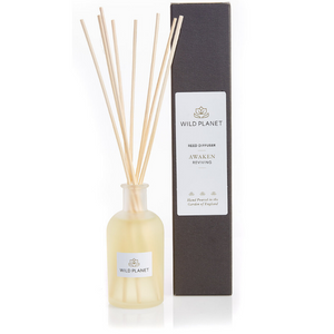Awaken Natural Reed Diffuser in glass bottle with 8 reed sticks next to branded black box