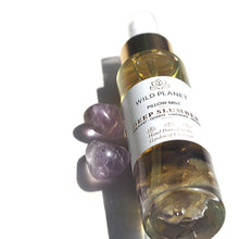 Deep Slumber Pillow Mist Bottle with amethyst crystals next to amethyst tumble stones