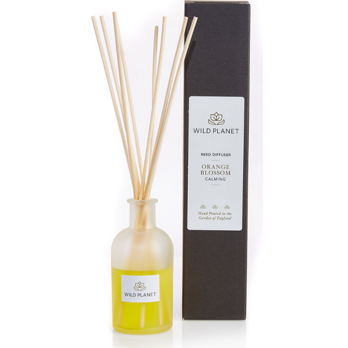 Orange Blossom Reed Diffuser glass bottle  next to tall black packaging by Wild Planet Products