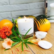 Lit Uplift Candle in Mood Boost on wooden table next to fresh fruit and flowers by Wild Planet
