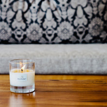 Lit Spice Night Candle on wooden coffee table next to grey and blue patterned sofa