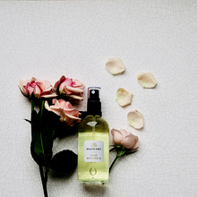 Rose Botanica - Rose Essential Oil Room Spray glass bottle next to fresh pink roses by Wild Planet